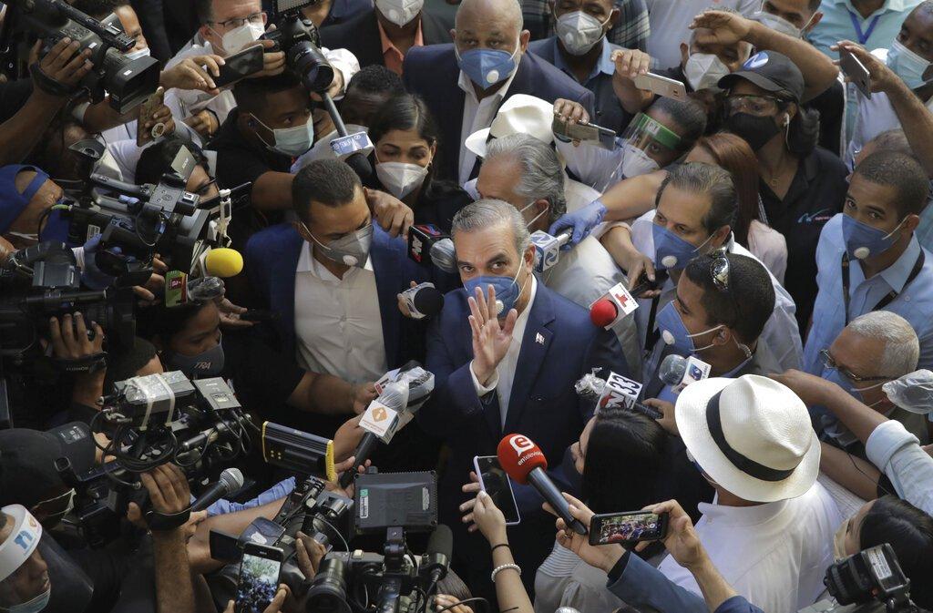 Luis Abinader, candidato presidencial del opositor Partido Revolucionario Moderno, saluda a la multitud mientras es rodeado por periodistas en un centro de votación durante las elecciones presidenciales, en Santo Domingo, República Dominicana, el domingo 5 de julio de 2020. (Foto AP/Tatiana Fernández)