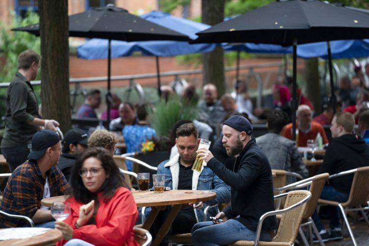 Personas sentadas en un bar en la calle Canal en la aldea gay de Manchester, Inglaterra, el sábado 4 de julio de 2020. (AP Foto/Jon Super)