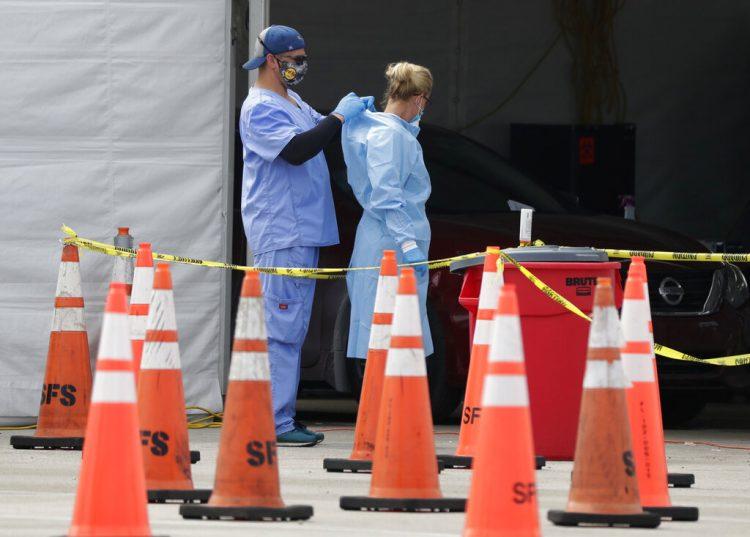 Trabajadores de la salud se ayudan mutuamente a colocarse equipo protector en un sitio de testeo del coronavirus en Miami Gardens, Florida, 5 de julio de 2020. El equipo protector para los trabajadores que atienden a enfermos de COVID-19 vuelve a escasear.  (AP Foto/Wilfredo Lee, File)