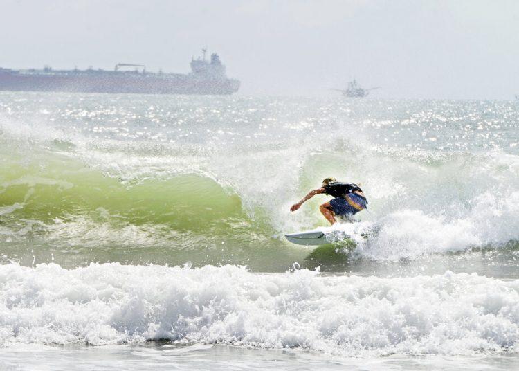 Un surfista se desplaza a orillas de la isla del Padre Sur el viernes 24 de julio de 2020 en medio de un mar picado debido a la tormenta tropical Hanna. (Miguel Roberts/The Brownsville Herald vía AP)