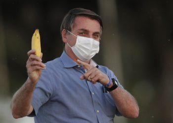 El presidente de Brasil Jair Bolsonaro señala un plátano a la prensa después de intentar dárselo de comer a un ñandú antes de iniciar la ceremonia de retiro de bandera afuera de su residencia oficial en el palacio Alvorada, en Brasilia, Brasil, el viernes 24 de julio de 2020. (AP Foto/Eraldo Peres)