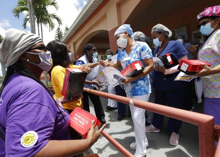 Trabajadores entregan cubrebocas para prevenir el contagio del coronavirus en una residencia y centro de rehabilitación de ancianos en Miami, 20 de julio de 2020. Foto: Wilfredo Lee/AP.