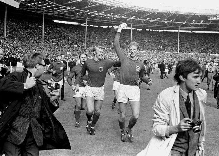 El 30 de julio de 1966 el inglés Jack Charlton sostiene la copa Jules Rimet mientras saluda al público en Wembley acompañado de su compañero Bobby Moore luego de derrotar 4-2 a Alemania Occidental. Foto: PA via AP.