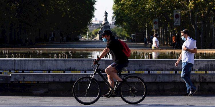 Un hombre circula en bicicleta y con mascarilla por el centro de la ciudad de Valladolid (España) donde este viernes las temperaturas superarán los 35 grados centígrados. Foto: EFE/Nacho Gallego.