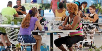 Varias personas comen este viernes 3 de julio de 2020 en la heladería Coppelia, durante el primer día de reapertura en La Habana desde que comenzó la pandemia de coronavirus. Foto: Yander Zamora / EFE.