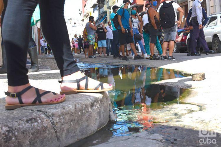 Compradores y policías en la cola en las afueras de la tienda de Prado 20, en La Habana, una de las nuevas tiendas que iniciaron la venta de artículos en Moneda Libremente (MLC) este lunes 20 de julio de 2020. Foto: Otmaro Rodríguez.