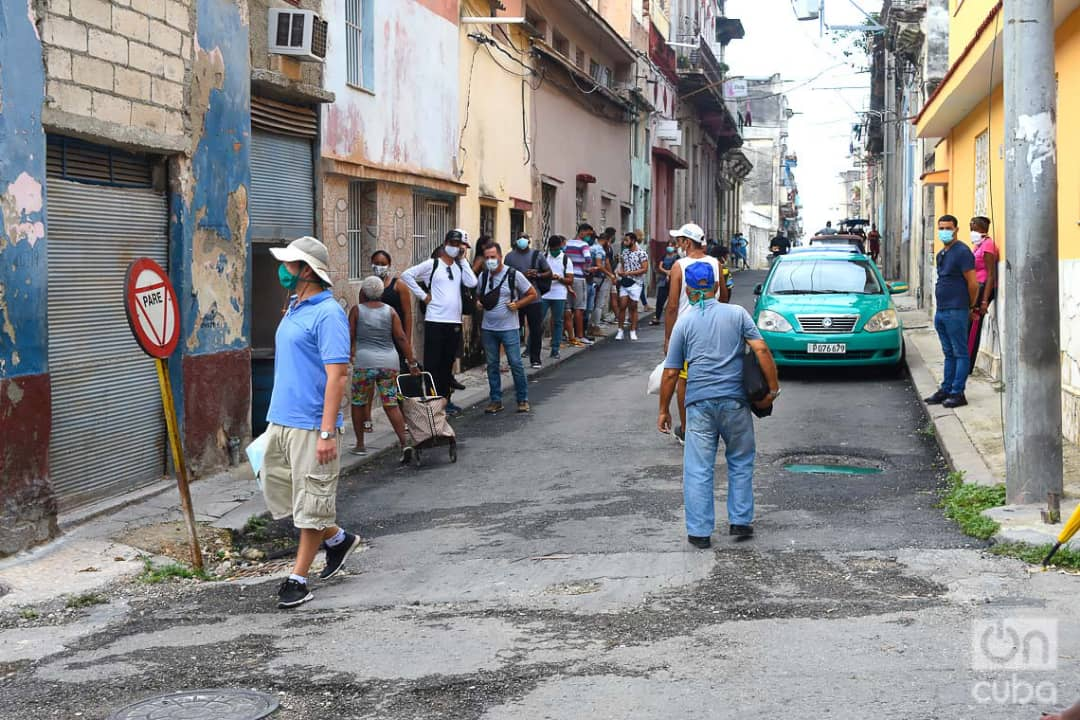 Compradores y policías en las afueras de la tienda La Cubana, de la calle Reina en La Habana, una de las nuevas tiendas que iniciaron la venta de artículos en Moneda Libremente (MLC) este lunes 20 de julio de 2020, como parte de las nuevas medidas económicas del gobierno cubano. Foto: Otmaro Rodríguez.