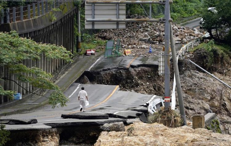 Un hombre camina por una carretera destrozada por el agua en Kumamura. Foto: AP/Koji Harada.