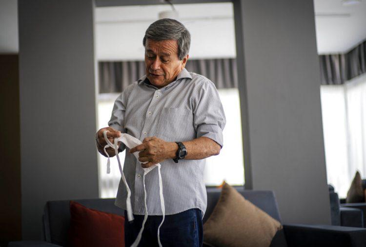 El comandante del Ejército de Liberación Nacional de Colombia (ELN), Pablo Beltrán, se quita el barbijo para protegerse del nuevo coronavirus antes de una entrevista en un hotel en La Habana, donde ha estado viviendo mientras se unía a las negociaciones con las autoridades colombianas que han estado suspendidas por más de un año, el miércoles 15 de julio de 2020. Foto: AP/Ramón Espinosa.