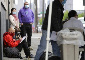 Una persona llena una solicitud de empleo durante una feria laboral en Seattle para la nueva línea de cubrebocas. Foto: Ted S. Warren/AP.