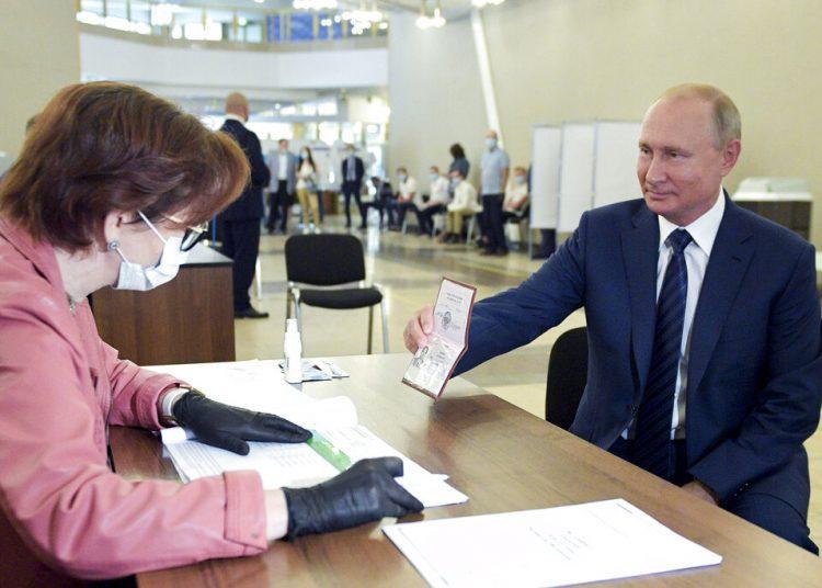El presidente ruso Vladimir Putin muestra su pasaporte a una trabajadora electoral poco antes de votar el miércoles 1 de julio de 2020, en Moscú. Foto: Alexei Druzhinin/Sputnik vía AP.