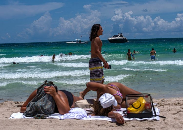 Decenas de personas disfrutan la playa este miércoles, en South Beach, en Miami La posible llegada a Florida de una tormenta tropical el fin de semana pone más presión a uno de los estados más golpeados por la COVID-19. Foto: Giorgio Viera / EFE.