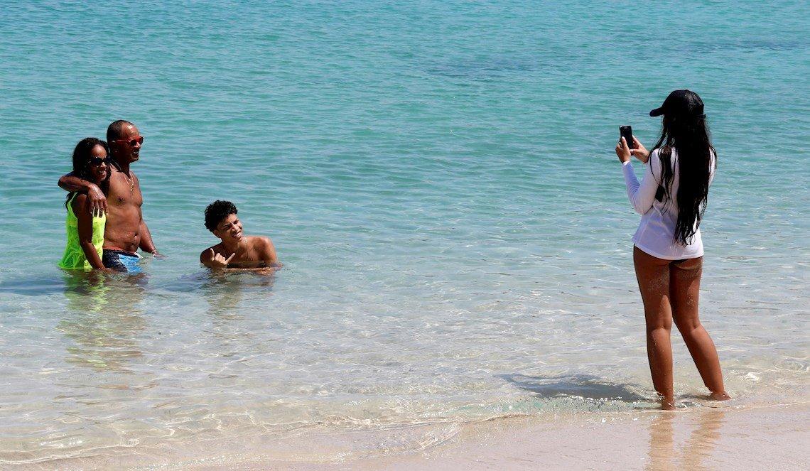 Varias personas se toman fotos mientras disfrutan este viernes 3 de julio de 2020 de un baño en la playa durante el primer día de reapertura en La Habana desde que comenzó la pandemia de coronavirus. Foto: Ernesto Mastrascusa /  EFE.