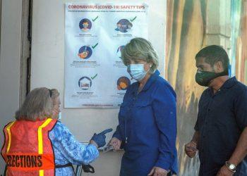 En día de elecciones primarias locales, dos electores se identifican en el centro de votación protegidos contra la pandemia. | Cristóbal Herrera / EFE