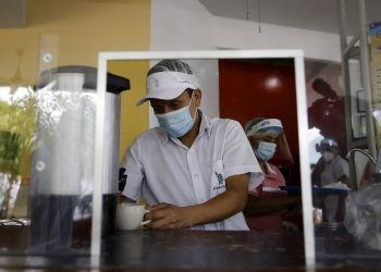 Trabajadores con mascarilla en un restaurante de El Salvador. Foto: Rodrigo Sura / EFE.