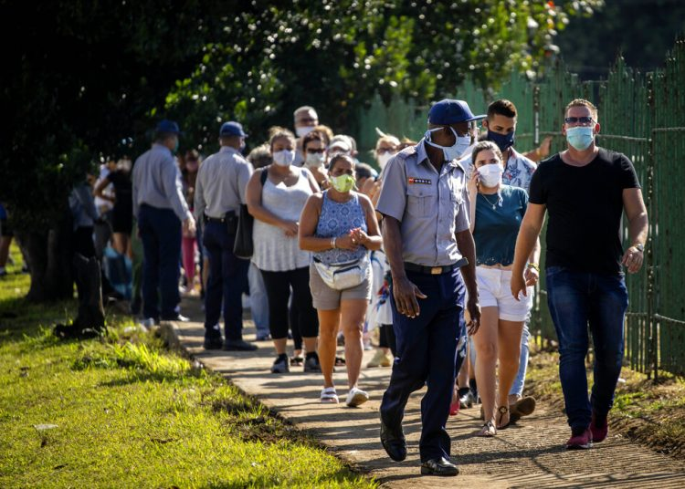 Personas con mascarillas en medio de la pandemia del nuevo coronavirus se forma para entrar a una tienda de alimentos en La Habana, Cuba. Foto: Ramon Espinosa/AP.