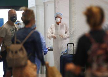 Personal médico espera para revisar a pasajeros en el aeropuerto Malpensa de Milán, el jueves 20 de agosto de 2020. (AP Foto/Antonio Calanni)