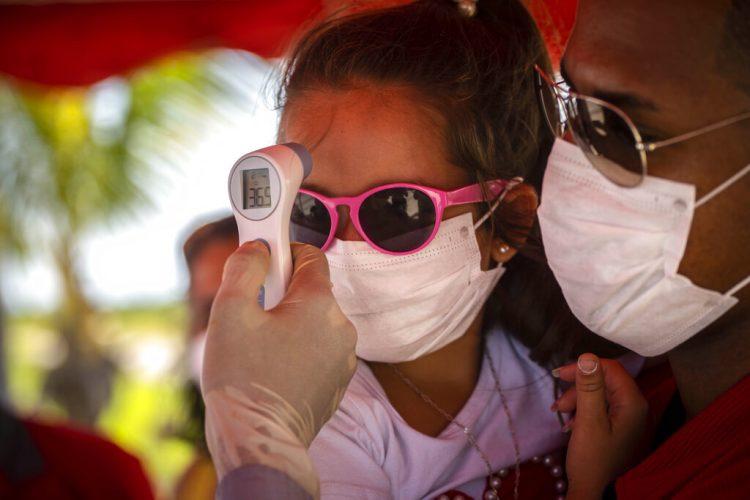 A una niña con mascarilla para protegerse del nuevo coronavirus le toman la temperatura en un puesto de control policial en la entrada de la provincia de La Habana, Cuba, el lunes 10 de agosto de 2020. Foto: AP/Ramón Espinosa.