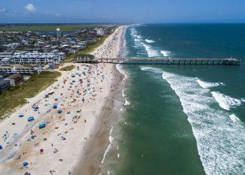 Bañistas en la playa de Wrightsville, Carolina del Norte, el domingo 2 de agosto de 2020, mientras la tormenta tropical Isaías avanza por la costa sureste del país. Foto: Travis Long/The News & Observer via AP.