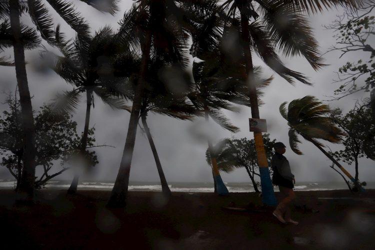 Una persona camina entre la lluvia y los fuertes vientos debido al paso de la tormenta Laura hoy, en Arroyo, sur de Puerto Rico. Foto: Thais Llorca/EFE.