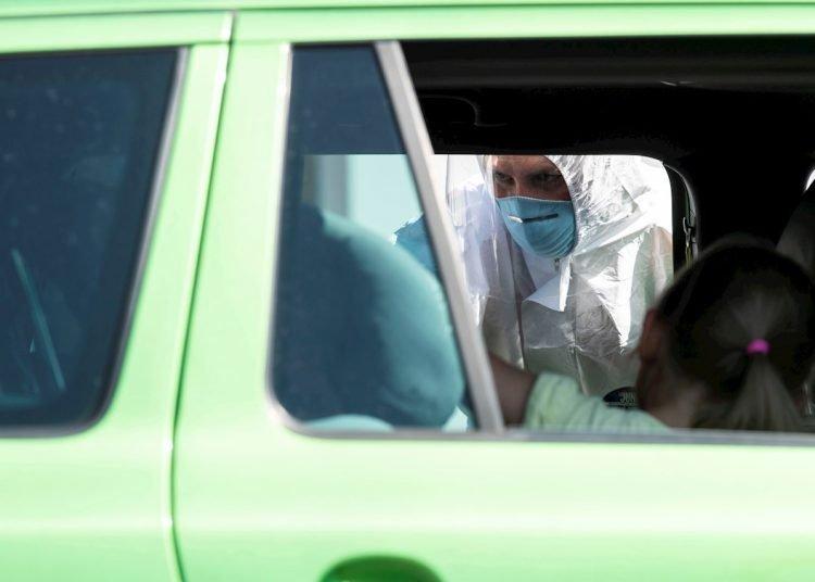 Un voluntario de la Cruz Roja Bávara realiza de manera gratuita la prueba para detectar la COVID-19 en un viajero. Cerca de Bergen, Baviera, Alemania, el 30 de julio de 2020. Foto: LUKAS BARTH-TUTTAS/ EFE/EPA.