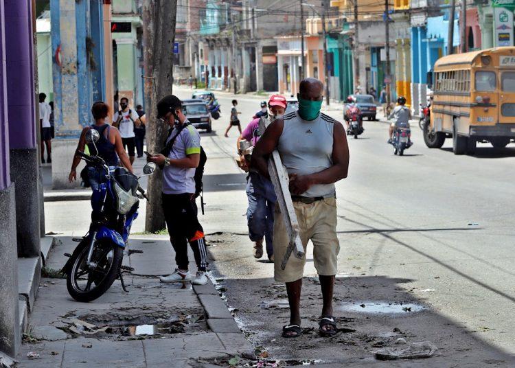 Varias personas caminan por una calle de La Habana tras el paso de la tormenta tropical Laura. Foto: Ernesto Mastrascusa/EFE.