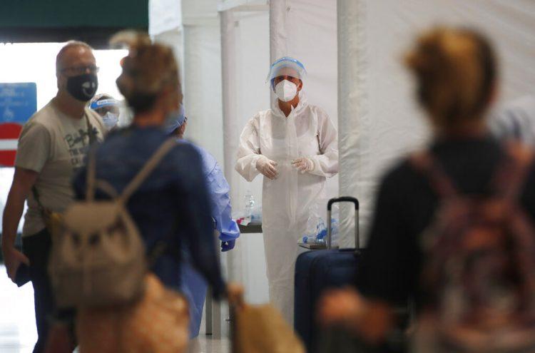 Personal médico espera para revisar a pasajeros en el aeropuerto Malpensa de Milán, el jueves 20 de agosto de 2020. Foto: Antonio Calanni/AP.