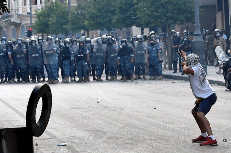 Un manifestante lanza piedras la policía antidisturbios libanesa con una honda durante una protesta en una de las carreteras que conducen al parlamento en Beirut, Líbano, el 10 de agosto de 2020. Gobierno libanés dimitió en medio de continuas protestas por la explosión del puerto de Beirut. Foto: WAEL HAMZEH/EFE/EPA.