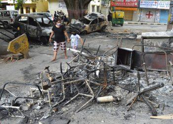 Una mujer y un niño pasan junto a los restos de vehículos y muebles quemados en las protestas de Bengaluru, India, el miércoles 12 de agosto de 2020. Al menos tres personas murieron en la ciudad en choques entre la policía y manifestantes que protestaban por una publicación de Facebook que consideraban como una ofensa al islam. Foto: AP.