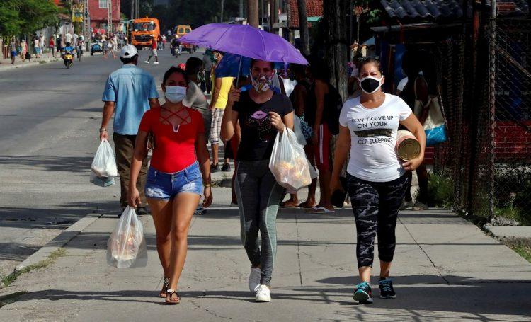 Personas con mascarillas en La Habana, durante la pandemia de la COVID-19. Foto: Ernesto Mastrascusa / EFE.