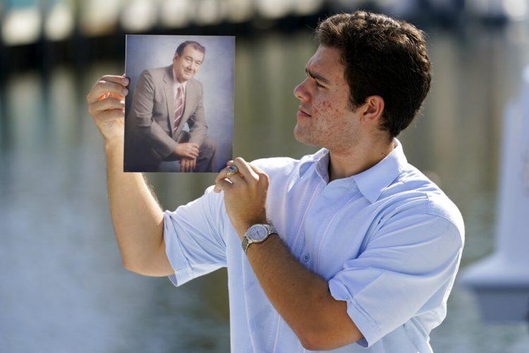 Freddy Vallejo Jr. muestra una foto de su abuelo Jorge Vallejo, el patriarca de la familia, un médico cubano que emigró e hizo su vida en la Florida. El abuelo y uno de sus hijos, Carlos, ambos médicos, fallecieron por el coronavirus. Foto: Lynne Sladky / AP.