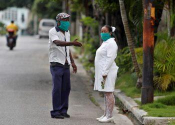 Un hombre y una trabajadora de la salud, cubiertos con tapabocas, fueron registrados este jueves al conversar en una calle de La Habana. Foto: EFE/Yander Zamora.