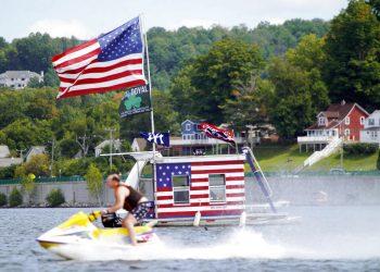 Una persona pasa con su moto acuática frente a un bote adornado con banderas estadounidenses en Pittsfield, Massachusetts, el lunes 7 de septiembre de 2020. Foto: Ben Garver/The Berkshire Eagle vía AP.