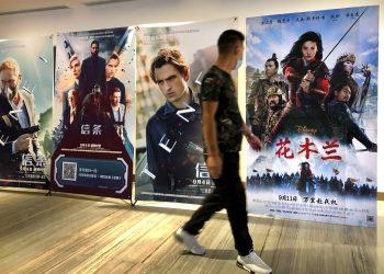"""Un hombre con mascarilla pasa junto a un afiche de la película de Disney """"Mulan"""" en un cine en Beijing, el 11 de septiembre del 2020.  Foto: Mark Schiefelbein/AP."""