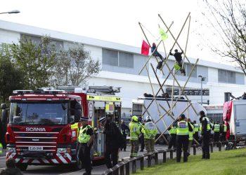 Policías y bomberos movilizados ante una imprenta de Broxbourne, donde varios manifestantes bloquean la carretera con una estructura, en Broxbourne, Hertfordshire, Inglaterra, el sábado 5 de septiembre de 2020. Foto: Yui Mok/PA via AP.