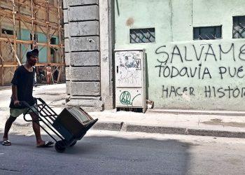 Un joven con nasobuco lleva un televisor en una carretilla, en La Habana. Foto: Ernesto Mastrascusa / EFE.