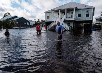 Una familia intenta cruzar una calle en Orange Beach, Alabama, inundada por el huracán Sally. Foto: Dan Anderson / EFE.