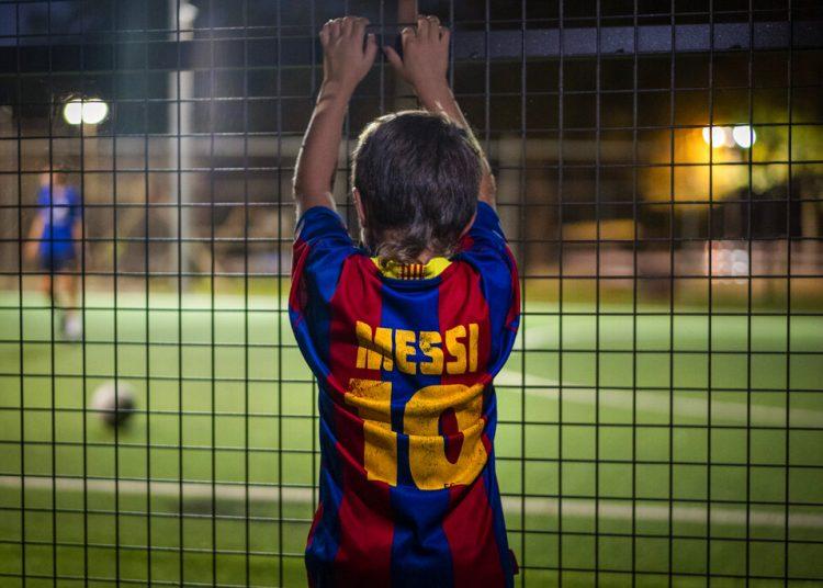 Un niño con una camiseta de Lionel Messi observa un partido de fútbol en Banyoles, España. Foto: Emilio Morenatti/AP/archivo.