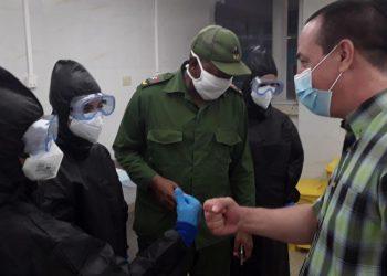 José Ángel Portal (d), ministro cubano de Salud Pública, saluda a dos trabajadoras del nuevo laboratorio de biología molecular abierto en la ciudad de Morón, en la central provincia de Ciego de Ávila, el 2 de octubre de 2020. Foto: ACN.