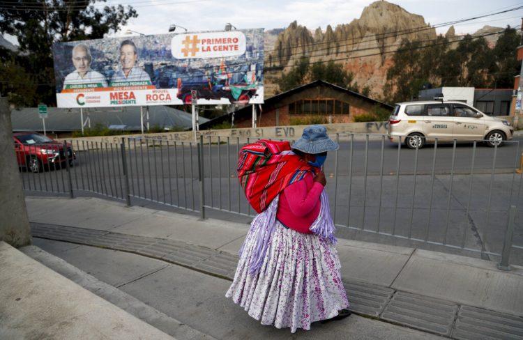 Una mujer camina cerca de una valla con propaganda electoral en El Alto, Bolivia, el sábado 17 de octubre de 2020. Foto: Juan Karita/AP.