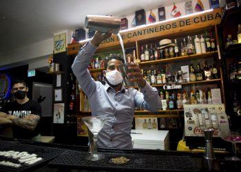 Con máscaras para protegerse del nuevo coronavirus, el bartender Dagoberto Jesús Morejón prepara un cóctel con plantas endémicas de Cuba, mientras su socio Manuel Alejandro Valdés lo respalda en La Habana, Cuba, el martes 13 de octubre de 2020. Foto: AP/Ismael Francisco.