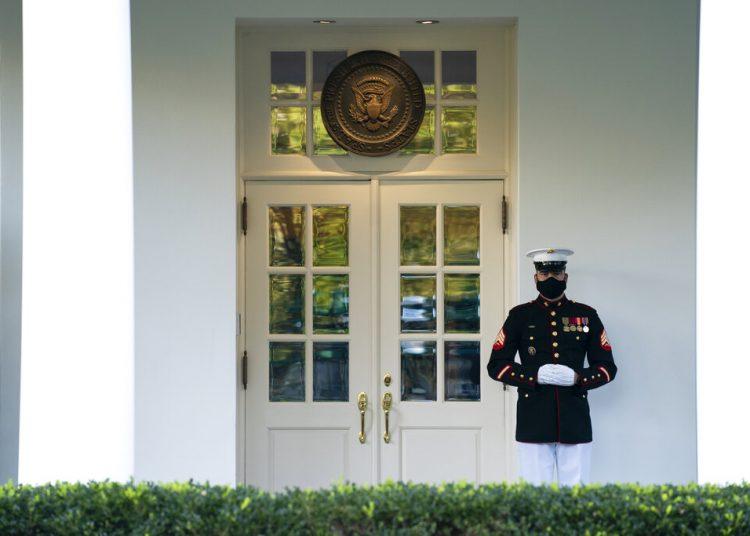 En esta foto del 8 de octubre del 2020, un marine monta guardia en el portal de la Casa Blanca, en Washington. Las campañas del presidente estadounidense Donald Trump y su rival demócrata Joe Biden están armando sendos grupos de abogados poderosos para la posibilidad de que la contienda por la Casa Blanca no sea decidida en las urnas, sino en las cortes. Foto: Evan Vucci/AP.