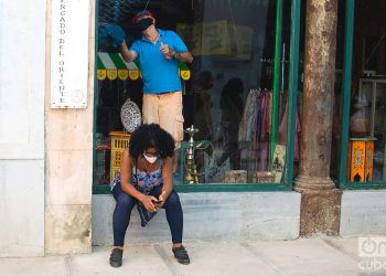Una mujer revisa su teléfono móvil en las afueras de una tienda que se prepara para su reapertura, tras la flexibilización de las restricciones por la COVID-19 en La Habana. Foto: Otmaro Rodríguez.