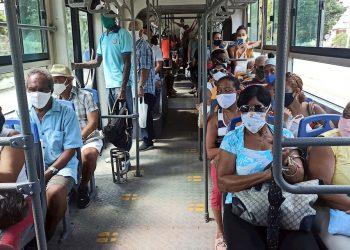 Decenas de personas usan este lunes tapabocas mientras van en un bus de transporte urbano, en La Habana (Cuba). Foto: EFE/Ernesto Mastrascusa.
