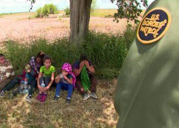 Un agente de ICE custodia a tres niños en la frontera. Foto: UN-ONU.