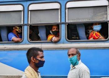 Pasajeros, con mascarilla para protegerse del coronavirus, esperan en el interior de un autobús mientras dos peatones cruzan por delante, en una estación de buses en Calcuta, India, el 1 de octubre de 2020. Foto: AP Foto/Bikas Das.