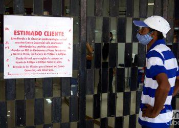 Un hombre lee un cartel colocado en la puerta principal del centro comercial Plaza Carlos III, en La Habana. Foto: Otmaro Rodríguez.