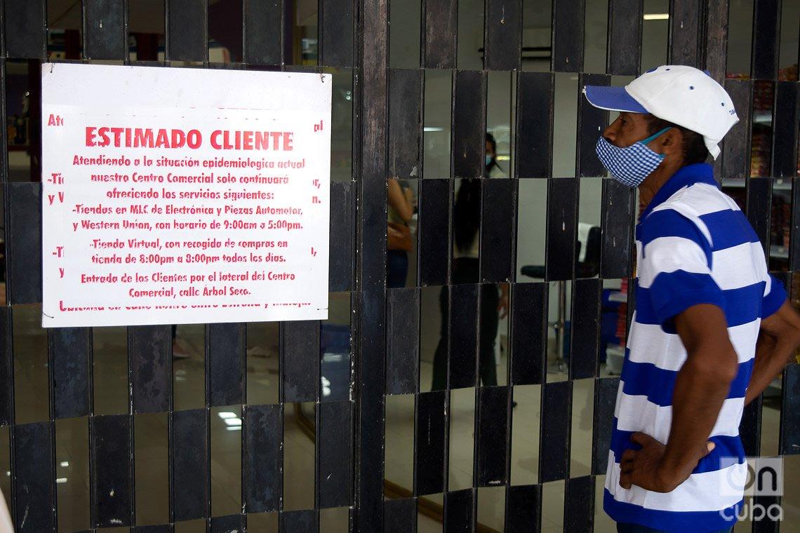 Un hombre lee un cartel colocado en la puerta principal del centro comercial Plaza Carlos III, en La Habana, que reabrió parcialmente con ventas en moneda libremente convertible. Foto: Otmaro Rodríguez.