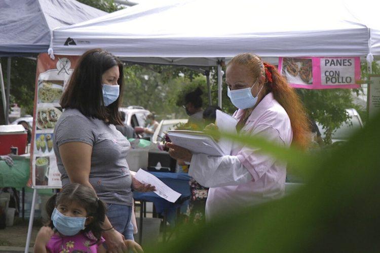 Una promotora de CASA, un grupo activista hispano, busca voluntarios latinos para probar una posible vacuna contra el COVID-19, en un mercado de Takoma Park, Maryland, el 9 de septiembre de 2020. Foto: Federica Narancio/AP.