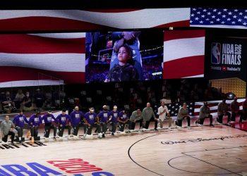 El 6 de octubre, integrantes de los Lakers de Los Ángeles se hincan durante el himno nacional antes del cuarto juego de las Finales de la NBA ante el Heat de Miami. Foto: John Raoux/AP.
